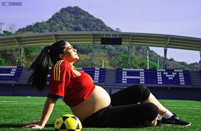 Kobieta w ciąży siedzi na boisku