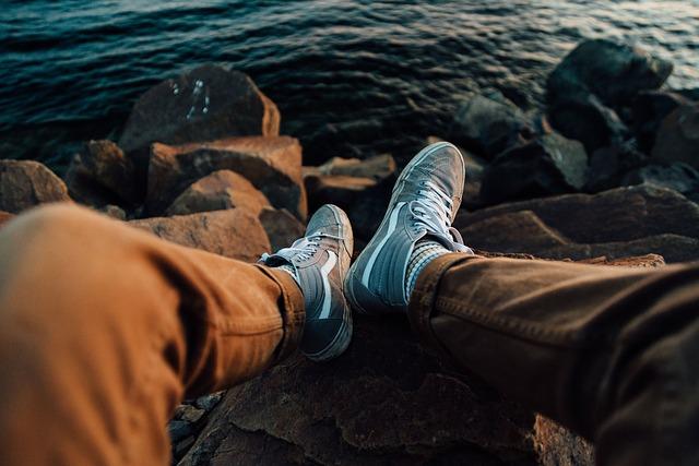 mężczyzna siedzący na skalistym brzegu